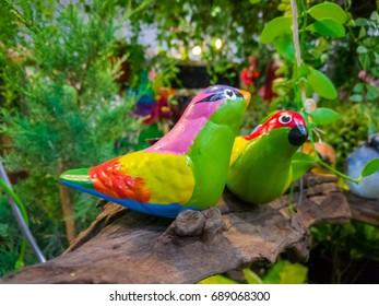 Ceramic parrot in the garden, parrot bird in garden, Parrot are standing on the branch in the garden