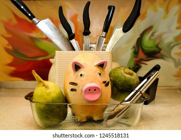 ceramic pig, standing in a frying pan surrounded by vegetables and kitchen utensils, fills the kitchen with humor