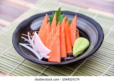 Ceramic plate with crab sticks or surimi and wasabi prepared for eating on table, traditional Japanese food.