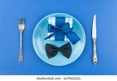 ceramic plate with a cutlery and gift box on the blue paper background. Concept Father's Day or Birthday background. Top view. International men's day concept.