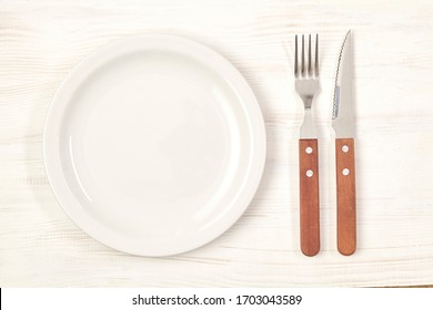Ceramic plate with fork and knife on wooden table. Top view.