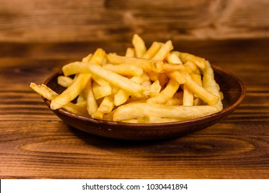 Ceramic plate with french fries on rustic wooden table