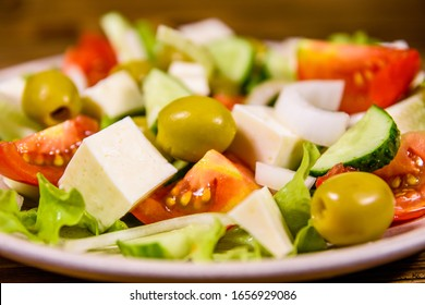 Ceramic plate with greek salad on rustic wooden table