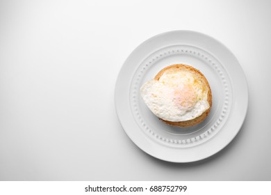 Ceramic plate with hamburger roll and over hard fried egg on light background