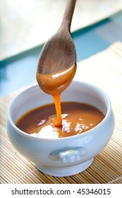 A ceramic pot of Cajeta, the famous mexican caramel sauce with ingredients and wooden spoon