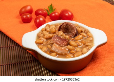 ceramic pot with carioca beans cooked (feijoada) on table with mat and cloth