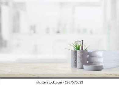 Ceramic shampoo bottle with white cotton towels on marble counter over bathroom background