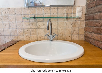 Ceramic sink with wooden table top and brick wall