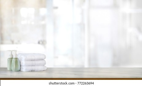 Ceramic soap green bottles and white cotton towels on a marble counter table inside a bright bathroom background.