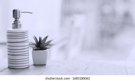 Ceramic soap, shampoo bottle with plant home on wood table