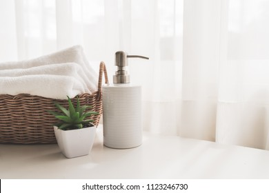 Ceramic soap, shampoo bottles and white cotton towels in basket on white counter table inside a bright bathroom background.