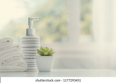 Ceramic soap, shampoo bottles and white cotton towels on white counter table inside a bright bathroom background.