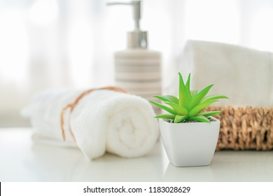 Ceramic soap, shampoo bottles and white cotton towels on white counter table inside a bright bathroom background