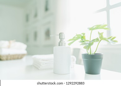 Ceramic soap, shampoo bottles and white cotton towels with green plants on white counter table inside a bright bathroom background, copy space For product display montage