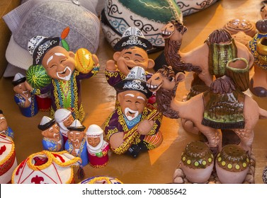 Ceramic souvenirs in street market. Smiling Kazakh & Kirghiz men & women in national costumes & camels. Caps & national hats in the background