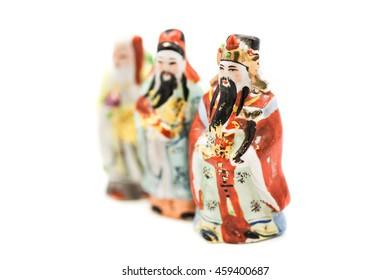 Ceramic Statue of Chinese Gods isolated on white background; God of Fortune (Fu,Hok), God of Prosperity (Lu,Lok), and God of Longevity (Shou,Siu), Focus on Lok