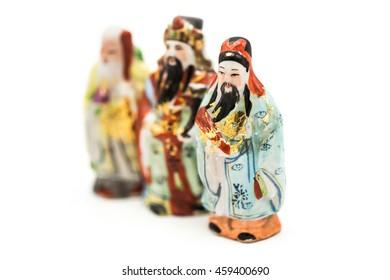 Ceramic Statue of Chinese Gods isolated on white background; God of Fortune (Fu,Hok), God of Prosperity (Lu,Lok), and God of Longevity (Shou,Siu), Focus on Hok