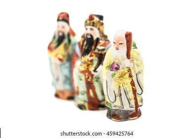 Ceramic Statue of Chinese Gods isolated on white background; God of Fortune (Fu,Hok), God of Prosperity (Lu,Lok), and God of Longevity (Shou,Siu), Focus on Siu