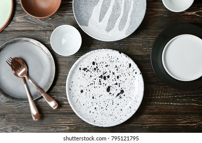 Ceramic tableware and cutlery on wooden background, top view