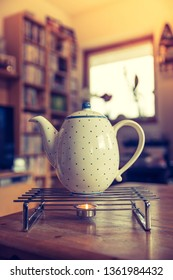 Ceramic tea pot with blue dots on a teapot warmer, winter time