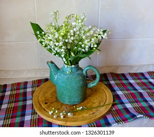 Ceramic teapot with bouquet of lilies of the valley
