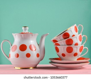 Ceramic teapot, a stack of cups in polka dots on a wooden table isolated on a blue pastel background. Copy space