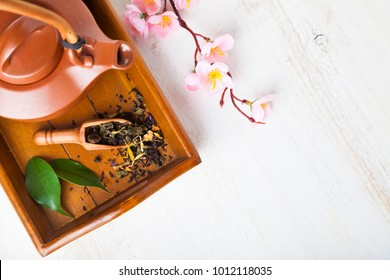 Ceramic teapot, tea leaves and sakura on a wooden tray, top view. Oriental tea.