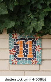 ceramic tile number eleven against brick wall