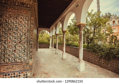 Ceramic tile walls and arabic arch, the 14th century Alcazar royal palace, Mudejar architecture style, Andalusia. UNESCO World Heritage Site, with Seville Cathedral. Spain.