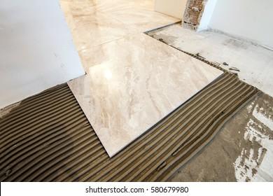 Ceramic tiles and tools for tiler. Floor tiles installation. Home improvement, renovation - ceramic tile floor adhesive, mortar, level.