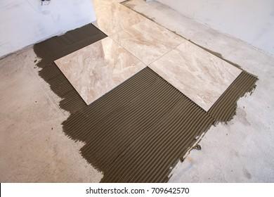Ceramic tiles and tools for tiler. Floor tiles installation. Home improvement, renovation - ceramic tile floor adhesive, mortar, level