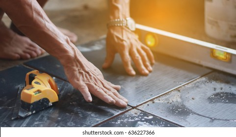 ceramic tiles. the worker's hand tile in position over adhesive with lash tile leveling system.selective focus.vintage tone