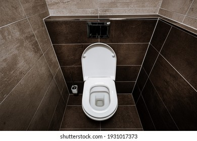 Ceramic toilet bowl with toilet seat, chrome wall button and toilet brush in restroom. Paving and tiling have texture of concrete trowel in shades of brown color. The toilet seat is open.