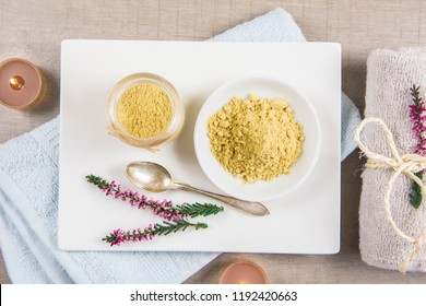 Ceramic tray with jar and bowl with mustard powder, towel and aroma candles to make foot bath. Against cold illness, congestion, aches and improves blood circulation. Alternative medicine concept.