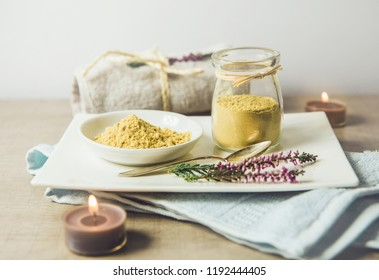 Ceramic tray with jar and bowl with mustard powder, towel and aroma candles to make foot bath. Against cold illness, congestion, aches and improves blood circulation. Vintage instagram style.
