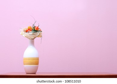 Ceramic vase with dry flowers on wooden table against purple wall
