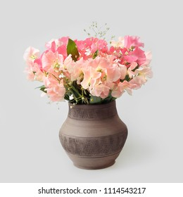 Ceramic vase with sweet pea (lathyrus odoratus) flowers on gray background