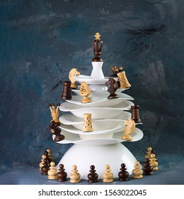 Ceramic white dishes Christmas tree decorated with chessmen on dark background. Square. Creative concept, postcard about hobby, invitation for New year party to chess club.
