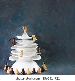 Ceramic white dishes Christmas tree decorated with chessmen on dark background. Square with copy space. Creative concept, postcard about hobby, invitation for New year party to chess club.
