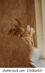 ceramic white vase with a beautiful bouquet of dried flowers on a beige background