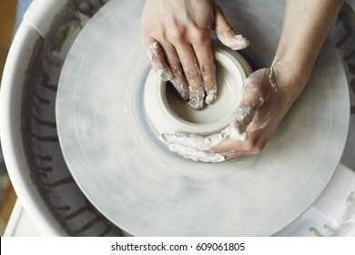 Ceramic working process with clay potter's wheel, close-up of woman hands