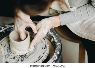 Ceramic working process with clay potter's wheel, close-up of female hands. Woman making pottery in studio.
