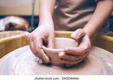 ceramic workshop - the girl makes a pot of clay on a potter's wheel. hands closeup