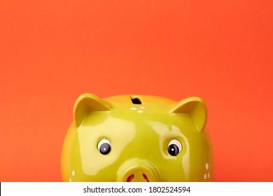 Keramikgelbe Spargel. Sparen des Geldkonzepts. Shiny-Sparschwein einzeln auf orangefarbenem Hintergrund.