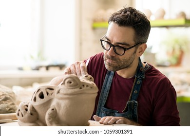 Ceramist Dressed in an Apron Sculpting Statue from Raw Clay in the Bright Ceramic Workshop.