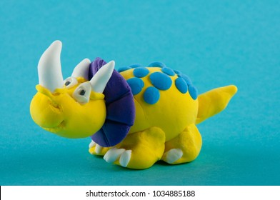 Ceratopsian. Funny yellow, blue, purple model of dinosaur staying on blue background