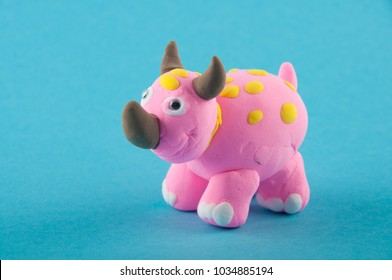 Ceratopsian. Pink, white, brown dinosaur figure made of modelling clay on blue background