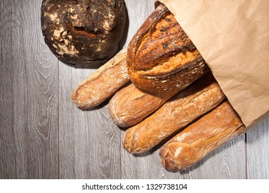 cereal baguette and buckwheat bread on paper bag