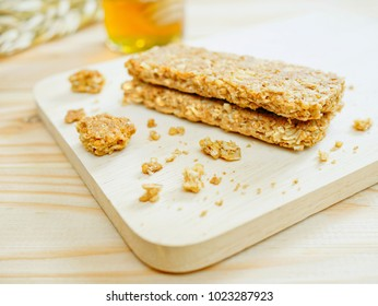 Cereal bars or flapjacks made from rolled oats with crumbs on wooden cutting board