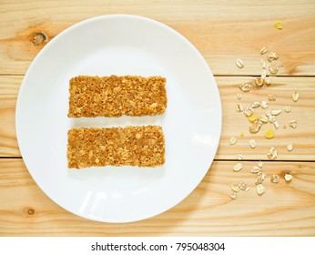 Cereal bars or flapjacks made from rolled oats on white plate. Top view.